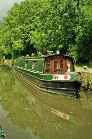 A green and red painted narrow boat on the local canal